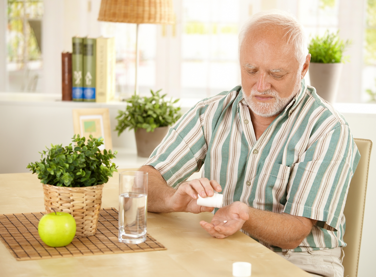 bigstock-Elderly-man-taking-pill-at-hom-14590277